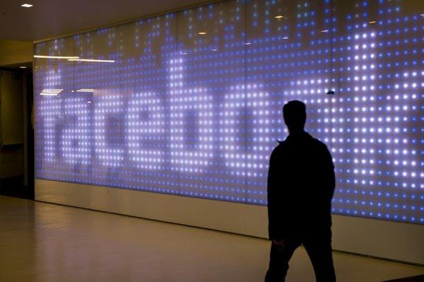An employee walks in front of a Facebook sign at Facebook's Menlo Park, Calif, headquarters.