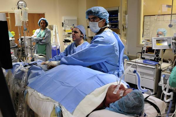 Dr. Mansour Razminia, second from left, performs a cardiac ablation on a patient who suffers from arrhythmia.  At right is cardiologist Roy Kiriakos, who is assisting on the surgery using 3-D mapping instead of X-rays.