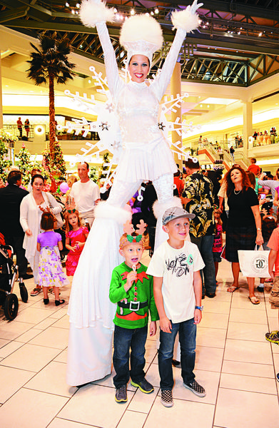 A performer poses with children during Santa's recent visit extravaganza, which took place at The Gardens Mall. More than 300 gifts were collected for The Salvation Army's annual toy drive.