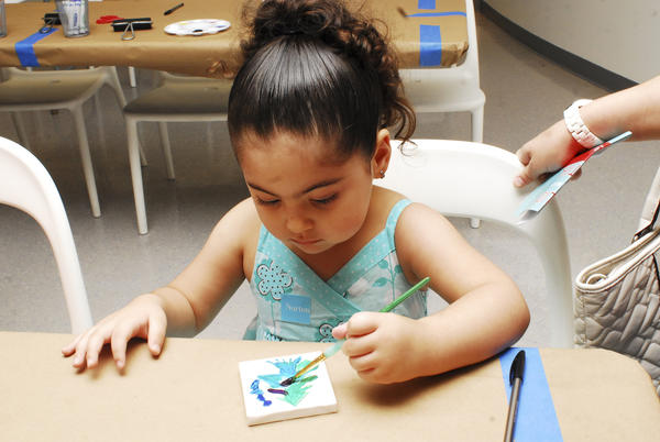 "Christina Cano, 3, paints a Christmas tree during the Norton Museum of Art's ""Holiday Family Festival,"" which took place Dec. 2 at the museum."