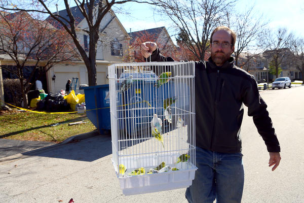George Hallenbeck of Greater Chicago Cage Bird Club holds a cage containing birds removed from a townhouse in Aurora.