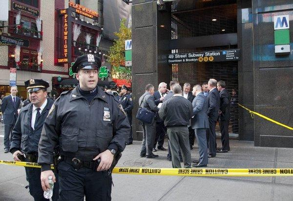Uniformed and plainclothes police officers gather outside the subway station in New York where witnesses say a man was killed after being pushed onto the tracks. A suspect has been picked up for questioning.