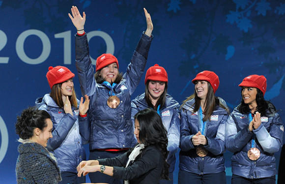 Lana Gehring raises her hands in celebration at 2010 Olympic medal ceremony.
