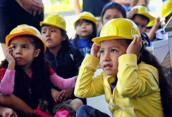 "Jacquelin Chavarrieta, 4, of Belle Glade, listens as Diane Pacheco of the Literacy Coalition reads the children's book, ""Goodnight Goodnight Construction Site""."