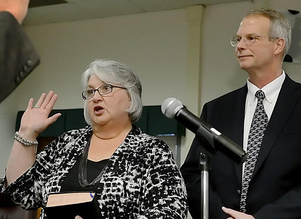 Melissa Willams, a newly elected political newcomer, is sworn in Tuesday as a member of the Washington County Board of Education while her husband David looks on.