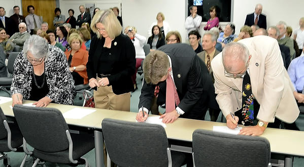 "The four newly elected Washington County Board of Education members, from left, Melissa Willams, left, Donna Brightman, Justin Hartings and Wayne Ridenour, sign a ""copy of oath"" Tuesday after being sworn in."