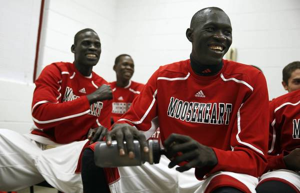 Mooseheart's Makur Puou (right), Mangisto Deng (left) and Akim Nyang (back) laugh while watching game tape before playing Westminster Christian. Earlier in the day, the three Sudanese student athletes were cleared by a Kane County judge to temporarily continue to play in games after the IHSA had declared them ineligible.
