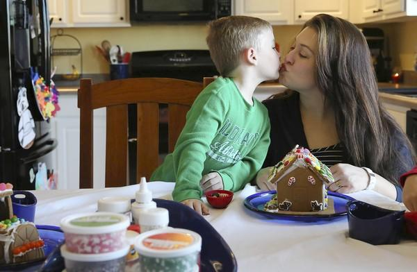 "Tina Peterson gets a kiss from her 5-year-old son, Brady, while the family decorates gingerbread at their home in Kenosha, Wis., Sunday. Peterson has employed the rule that Santa brings ""one want, one need, one wear, one read"" to her three children."