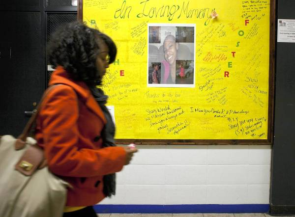 Joniqua Shaw walks past a memorial for Porshe Foster, 15, on Tuesday at ACE Tech Charter High School. Foster was fatally shot Nov. 26.