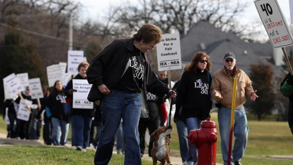 "District 300 teacher, Martha Black, an intervention teacher at Lakewood School, walks the picket line with her puppy ""Grace"" outside District 300 administrative offices in Carpentersville on Tuesday, December 4, 2012. A tentative 3-year contract was later reached."