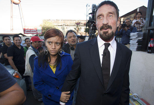 "Software company founder John McAfee, right, accompanied by his girlfriend ""Sam,"" exits a news conference outside the Supreme Court in Guatemala City on Tuesday. McAfee, 67, who has been identified as a ""person of interest"" in the killing of his neighbor in Belize, has surfaced in public for the first time in weeks, saying Tuesday that he plans to ask for asylum in Guatemala because he fears persecution in Belize, though it's unclear why he would need asylum because his travel has not been restricted."