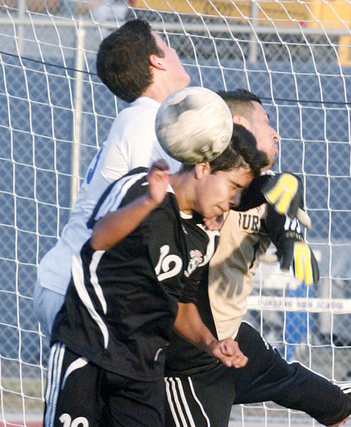 A collision in front of the Burbank goal with South Pasadena's Ramon Gutierrez attempting to put the ball passed Burbank keeper Arais Teimoorian and defender Joseph Servin in the first half in a non-league boys soccer game at Burbank High School on Tuesday, December 4, 2012.