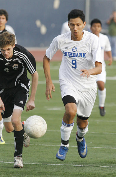 Burbank's Dennis Palacio drives toward the South Pasadena goal with South Pasadena defender Leo Oarker in pursuit in the first half in a non-league boys soccer game at Burbank High School on Tuesday, December 4, 2012.