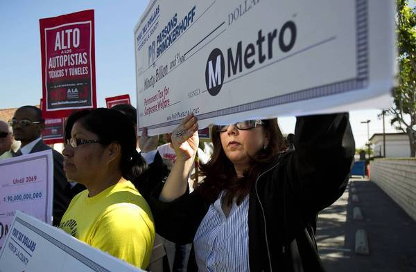 "Rosa Miranda, left, of the Bus Riders Union, and Lisa Korbatov of Beverly Hills hold blank ""checks"" highlighting Measure J's corporate sponsors and beneficiaries during a news conference against the transit tax in Los Angeles in advance of the Nov. 6 election. The Coalition to Defeat Measure J included the Bus Riders Union, the Beverly Hills Unified School District and others."