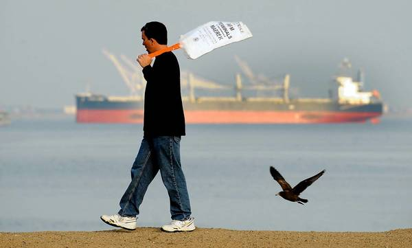 Since the strike began, a number of cargo ships have sat anchored outside the L.A. and Long Beach ports, waiting for a resolution to the labor dispute. Above, a picketer is shown Tuesday at the Port of Los Angeles.