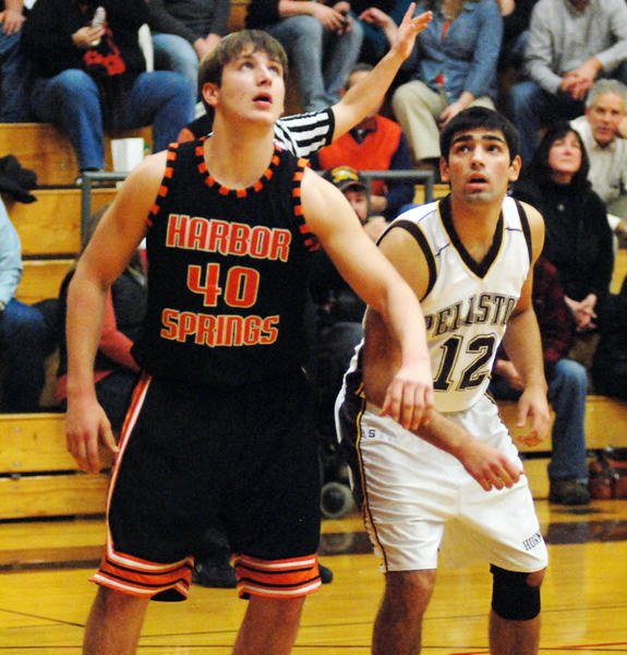 Harbor Springs senior forward Spencer Kloss (left) and Pellston senior Austin Wright eye the ball during a free throw attempt during Tuesdays non-league season opener at the Pellston High School gym. The Rams defeated the Hornets, 57-18, as Kloss finished with 24 points and eight rebounds.