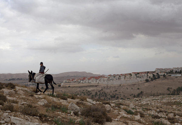 A Palestinian boy rides a donkey Wednesday in the E-1 area near the West bank settlement of Maale Adumim, background, on the eastern outskirts of Jerusalem.