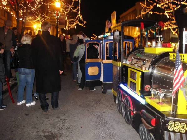 Parents help their children on to a kiddie train that traveled a village streeet during the Christmas Walk.
