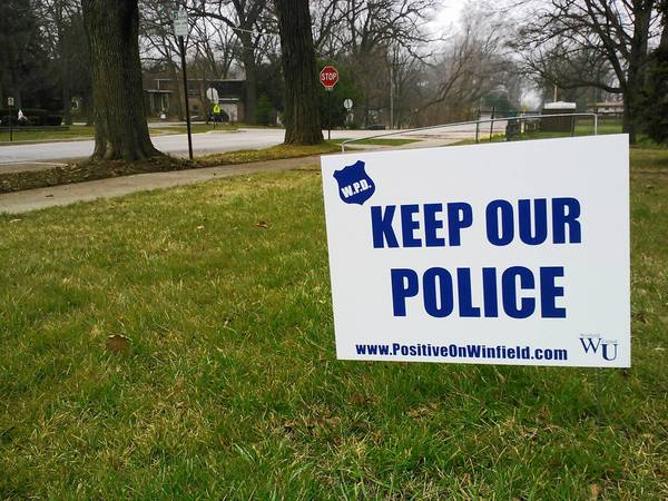 """Keep Our Police"" signs remain in Winfield lawns this month, demonstrating support for maintaining the village's police department."