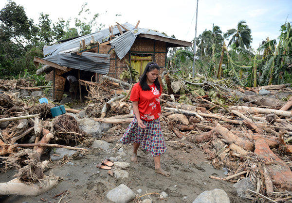 A woman walks amongst debris next to her damaged house in the village of Andap, New Bataan town, Compostela Valley province on Wednesday, a day after Typhoon Bopha hit the province.