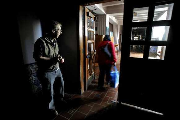 Glendale College superintendent/president Jim Riggs lets an employee out a dark main building on campus that remained closed due to an electrical outage at the main campus in Glendale on Wednesday, December 5, 2012.