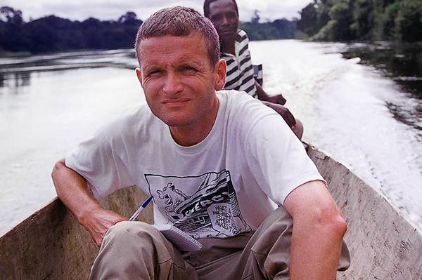 Paul Salopek taking notes in a pirogue (a dugout canoes made from a single log) on the Ivindo River outside of Makokou Gabon in 1999.