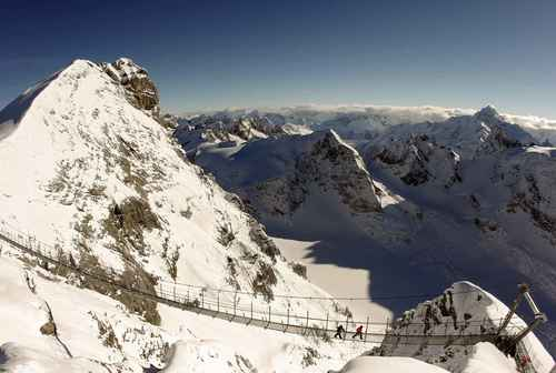 Construction workers walk over the Titlis Cliff Walk suspension bridge in front of the peak of Mt. Titlis near the Swiss mountain resort of Engelberg Dec. 1, 2012.