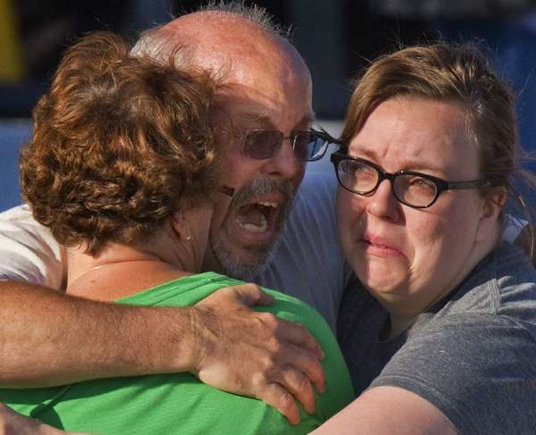 "Tom Sullivan, center, embraces family members after his son, Alex, who celebrated his 27th birthday by going to see ""The Dark Knight Rises,"" was among those killed in the Colorado movie theater shooting."