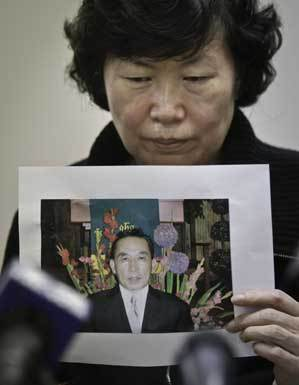 Serim Han holds a picture of her husband, Ki-Suck Han, who was killed by a train after being pushed onto the subway tracks.