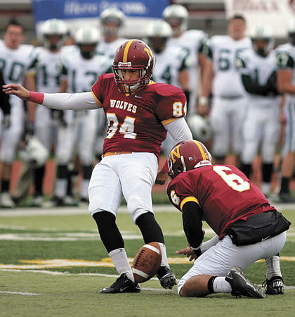 Northern State University's Felipe Alfaia (84) kicks the ball out of the hold of teammate Jared Jacobson (6) on a first half field goal attempt in a game at Swisher Field.