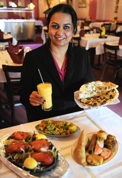 Amy Singh, co-owner of Nawab Indian Restaurant in south Bethlehem, with some of the traditional dishes in the dining room.