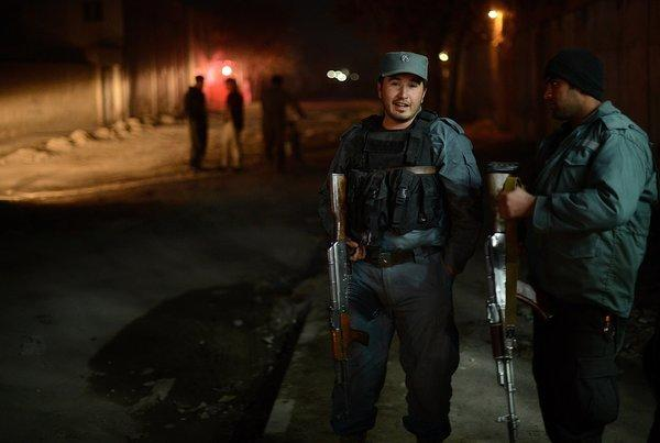 Afghan policemen block a road near the site of an attack at a spy agency guest house in Kabul, Afghanistan.