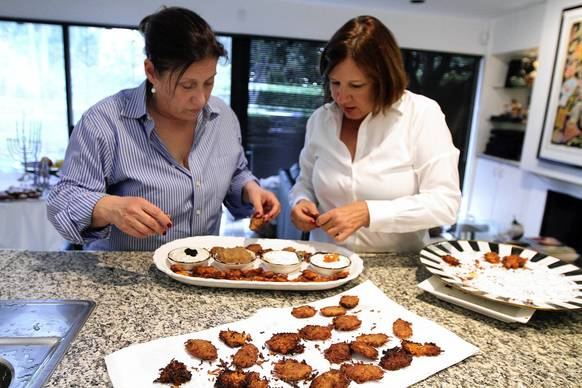 Joanie Besser, left and Nancy Gold, plate Potato latke after draining the oil, both originally from New Orleans, have been hosting an annual latke party for a dozen years in Boca Raton.