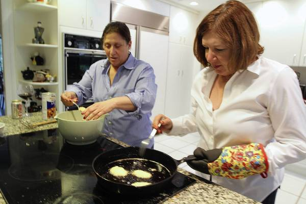 Joanie Besser, left and Nancy Gold making potato latke. Both originally from New Orleans, have been hosting an annual latke party for a dozen years in Boca Raton.