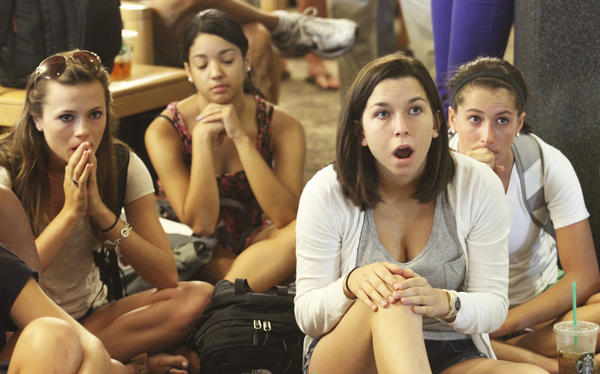 Penn State University student Laura Lovins, (2nd R) and fellow students react while watching a live broadcast of the announcement of the NCAA penalties and sanctions.