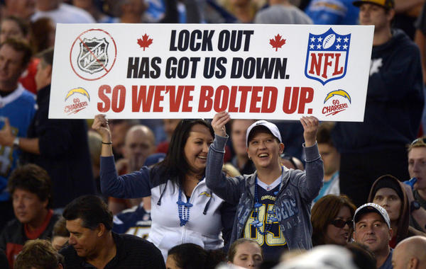 "Fans of the NHL and the San Diego Chargers hold a sign that reads ""Lock out has got us down so we've bolted up"" during the game against the Kansas City Chiefs at Qualcomm Stadium."
