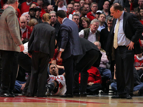 Injured Chicago Bulls point guard Derrick Rose (1) is attended to by medical staff during the fourth quarter in the Eastern Conference quarterfinals of the 2012 NBA Playoffs against the Philadelphia 76ers at the United Center. The Bulls won 103-91.