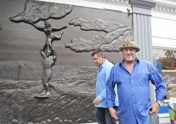 Sculpture artist Randy Morgan, right, stands proud next to the Waterman's Wall sculpture after unveiling it to the public Thursday. The mural is dedicated to Laguna Beach's surfing and ocean sports heritage.