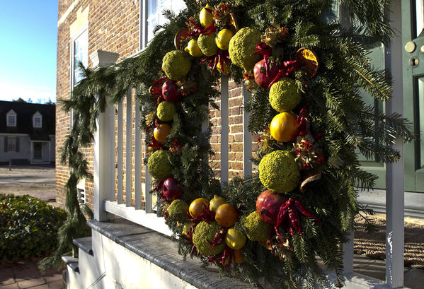 Colonial Williamsburg shows off their Christmas decorations.	Roscow Cole House- Hunter Curry created this large Dela robia style wreath to accent the large façade of the brick house.  This porch is used for the Williamsburg town¿s Christmas Eve celebration, so it is a very ornate piece for this special occasion.  Materials include osage oranges, red chili peppers, safflower, lemons, oranges, pomegranates and sliced quince.