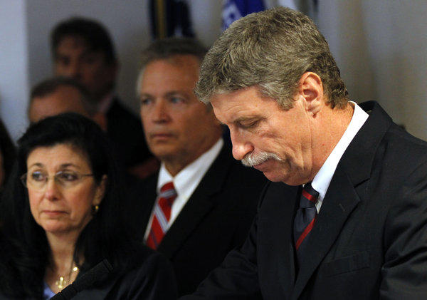 Federal prosecutor Jim Letten announces his resignation during a news conference in New Orleans. At far left is his wife, JoAnn.