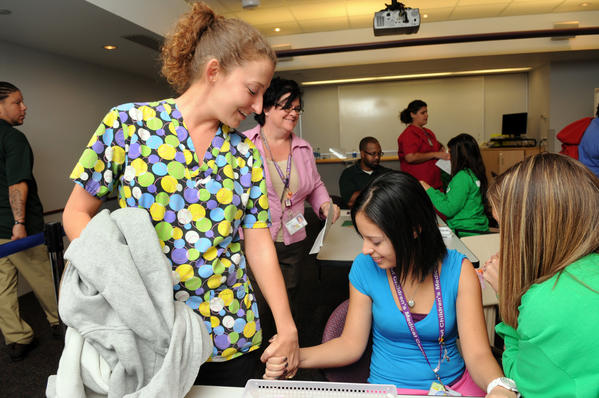Jennifer Tennyson of Rocky Hill, left, holds hands with friend and hospital co-worker Leslie Rodriguez of Hartford as she gets a flu shot from RN Sarah Matney at Connecticut Children's Medical Center in October 2011.