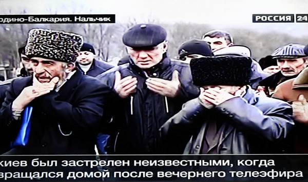 An image from Russian TV shows relatives and friends mourning slain TV journalist Kazbek Gekkiyev, 28, at a cemetery in Nalchik. He was allegedly approached by two gunmen who killed him after he confirmed his identity.