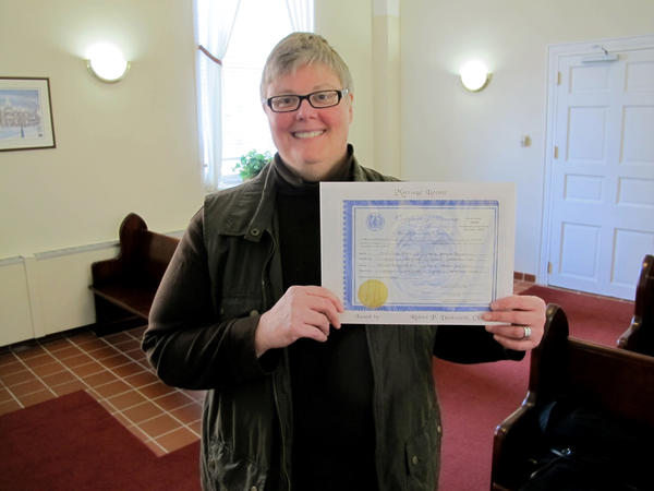 Kim Hinken, of Edgewater, Md., holds the marriage license she obtained Thursday in Anne Arundel County Circuit in Annapolis, to marry her same-sex partner, Adrianne Eathorne. It was the first day same-sex couples could get a Maryland marriage license, which will be effective Jan. 1, when the law takes effect. Hinken, pictured in the courthouse chapel, was the first person to get a same-sex marriage license in Anne Arundel County.
