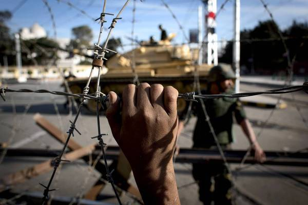 Barbed wire and tanks surround the presidential palace in Cairo, while protesters outside the barrier chant slogans against President Mohamed Morsi.