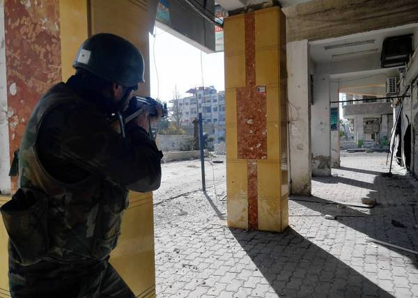 In a photo recently released by the official Syrian Arab News Agency, a government soldier takes aims during a battle in the Damascus suburb of Dariya.