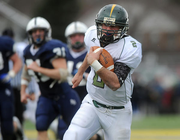 Central Catholic's Colin McDermott (right) runs through the Abington Heights' defense for a touchdown during their PIAA 3A playoff game Saturday afternoon.