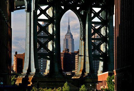 New York's Empire State Building is framed by the Manhattan Bridge.