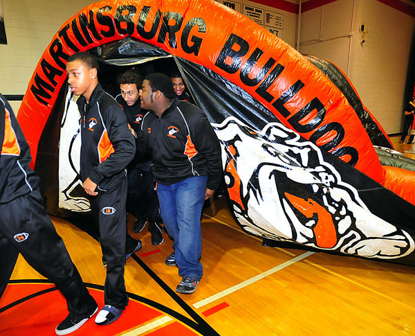 Players on the Martinsburg High School football team enter the school's gym Thursday night for a celebration of the team's third consecutive West Virginia Class AAA state championship.