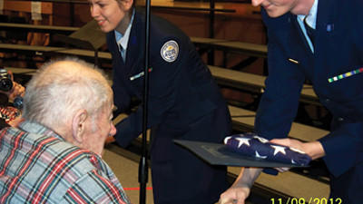 John Barnick is honored with a flag by Reserve Officers' Training Corps leaders at Somerset high school Nov. 9 at the annual Veterans Day assembly.