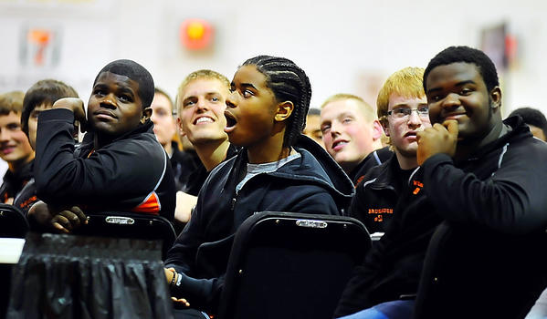 Martinsburg (W.Va.) High School football player Corey Barnhardt, center, reacts to his name being mentioned Thursday night while watching a highlight video of the team's third straight state championship.